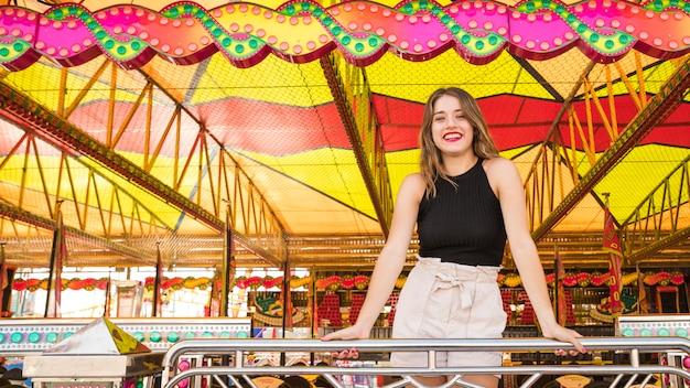 Souriante jeune femme debout derrière la rambarde au parc d'attractions