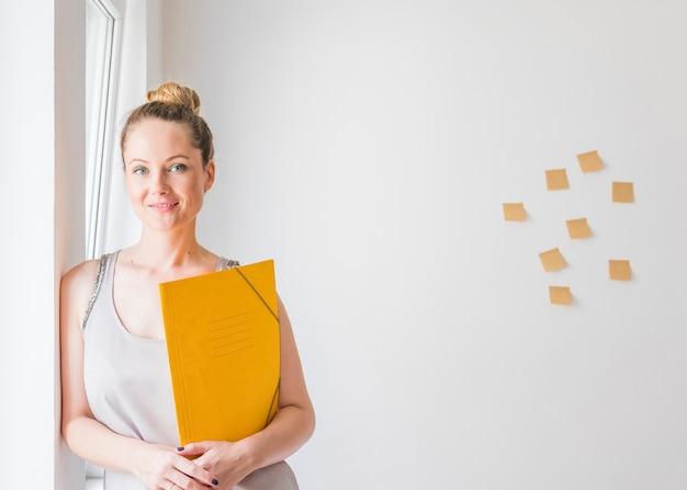 Souriante jeune femme debout devant un mur tenant des dossiers jaunes