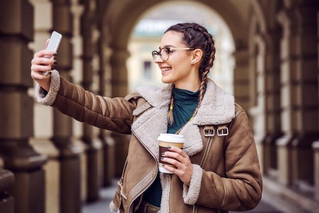 Souriante jeune femme debout à l'extérieur, tenant une tasse jetable avec du café et prenant selfie.