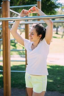 Souriante jeune femme debout près des barres de singe