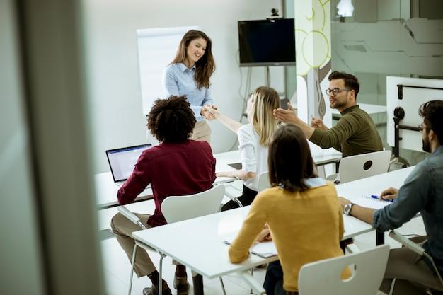 Souriante jeune femme debout près du tableau blanc et serrant la main à sa collègue