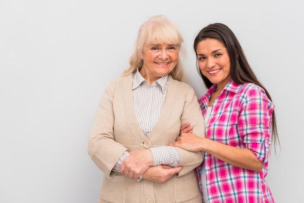 Souriante jeune femme debout avec sa mère sur fond blanc