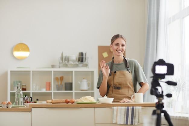 Souriante jeune femme debout à la table de la cuisine et agitant ses mains pendant le tournage de la vidéo