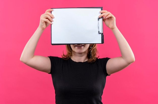 Souriante jeune femme décontractée soulevant le presse-papiers et se cachant derrière elle sur un espace rose isolé