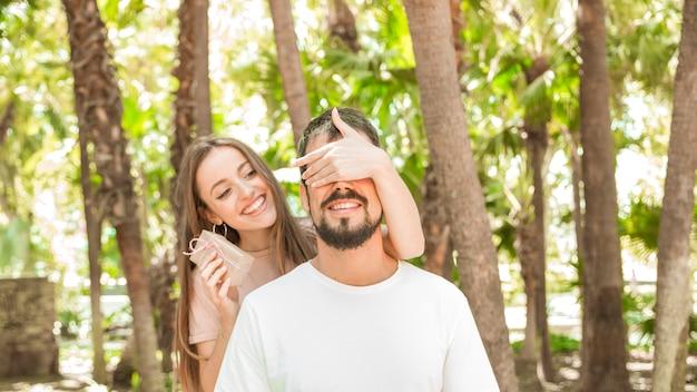 Souriante jeune femme donnant un cadeau surprise à son petit ami en forêt