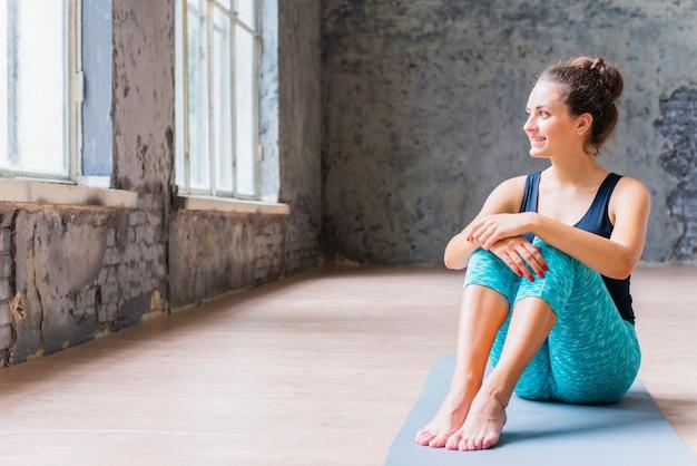 Souriante jeune femme dormant sur un tapis d'exercice