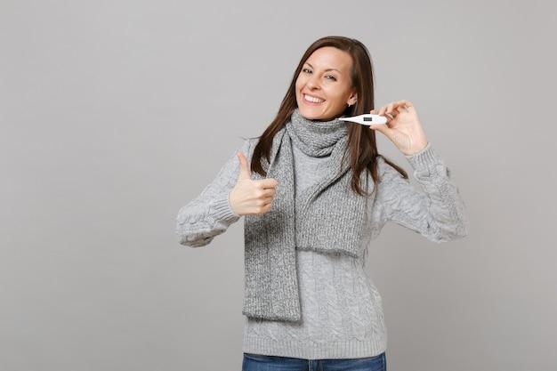 Souriante jeune femme en écharpe pull gris montrant le pouce vers le haut tenant un thermomètre isolé sur fond de mur gris. mode de vie sain, traitement des maladies malades, concept de saison froide. maquette de l'espace de copie.