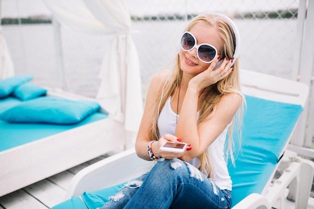 Souriante jeune femme écoutant de la musique sur une chaise longue