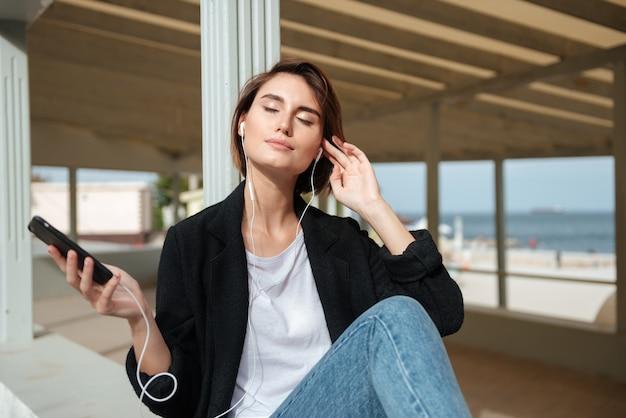 Souriante jeune femme écoutant de la musique depuis un téléphone mobile dans une véranda au bord de la mer