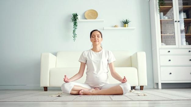 Souriante jeune femme enceinte en blanc médite assise en position de yoga padmasana sur le sol contre des meubles design dans une pièce spacieuse à la maison