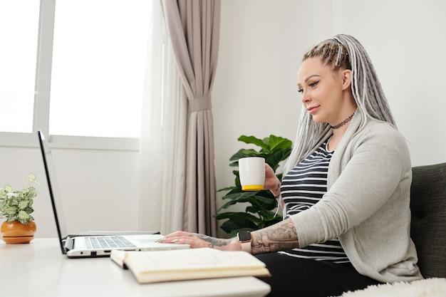 Souriante jeune femme enceinte buvant une tasse de thé et regardant un webinaire sur un ordinateur portable lorsqu'elle étudie à la maison en raison de la pandémie de coronavirus