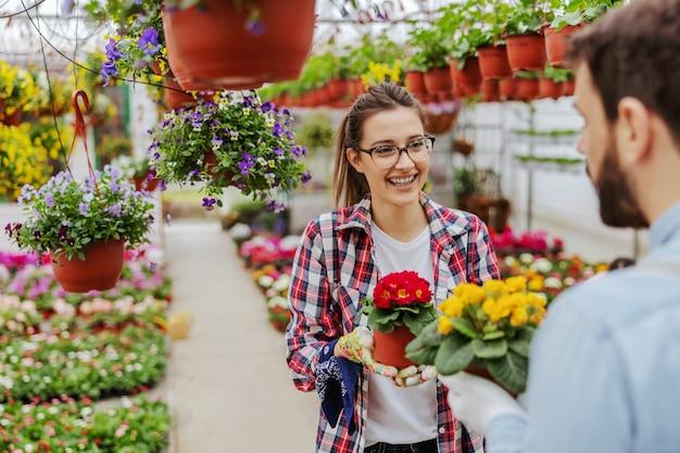 Souriante jeune femme entrepreneur debout avec des fleurs dans les mains et en regardant son partenaire. concept de petite entreprise.