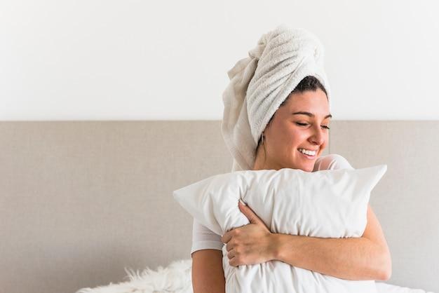 Souriante jeune femme enveloppant sa tête avec une serviette tenant un oreiller blanc