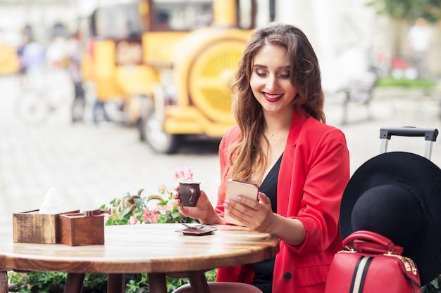 Souriante jeune femme est assise dans un café de la ville et regarde au téléphone.