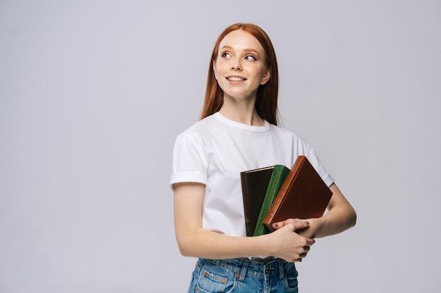Souriante jeune femme étudiante tenant des livres et rêveuse regardant loin sur fond isolé