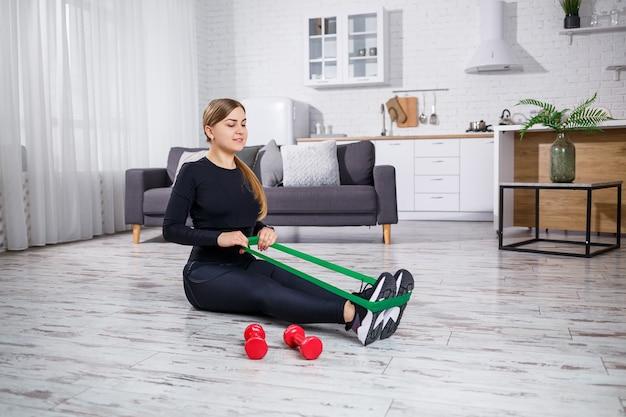 Souriante jeune femme exerçant avec une bande élastique à l'entraînement de remise en forme à domicile. concept de mode de vie sain. faire du sport à la maison pendant le confinement