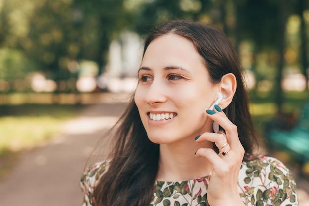 Souriante jeune femme à l'extérieur dans le parc de la ville utilisant des écouteurs et écoutant de la musique ou parlant au téléphone