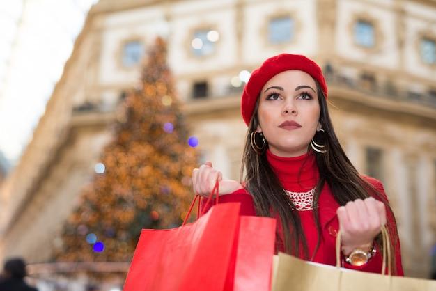 Souriante jeune femme faisant du shopping dans une ville avant noël