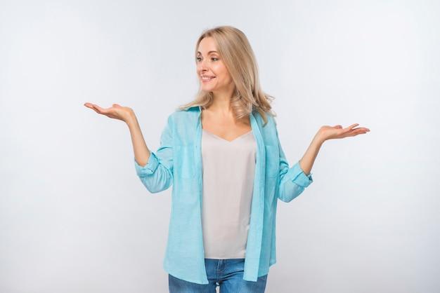 Souriante jeune femme haussant les épaules isolé sur fond blanc
