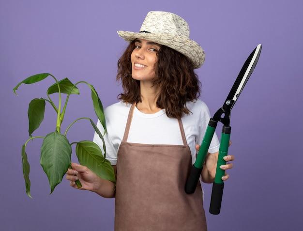 Souriante jeune femme jardinière en uniforme portant chapeau de jardinage holding plant plante avec tondeuses