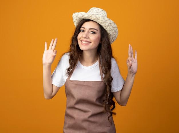 Souriante jeune femme jardinière en uniforme portant des gestes de chapeau de jardinage signe de la main ok avec deux mains isolé sur un mur orange avec espace de copie