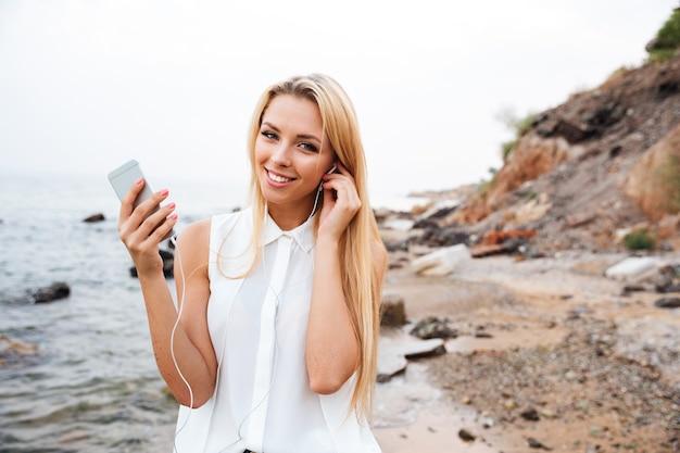 Souriante jeune femme jolie écoute de la musique avec smartphone en se tenant debout sur la plage rocheuse