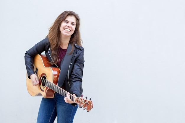 Souriante jeune femme jouant de la guitare