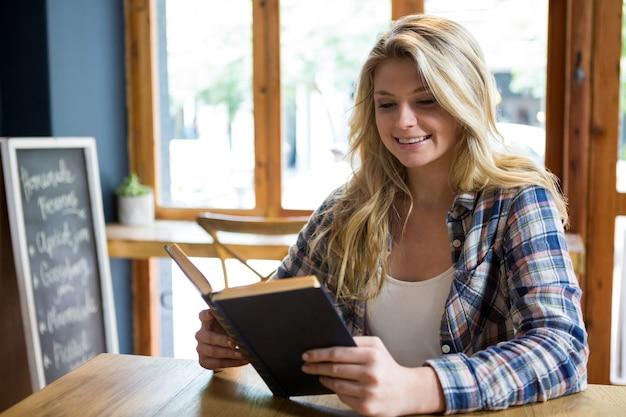 Souriante jeune femme lisant un livre à table dans un café