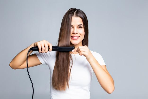 Souriante jeune femme lissant ses cheveux avec du blanc