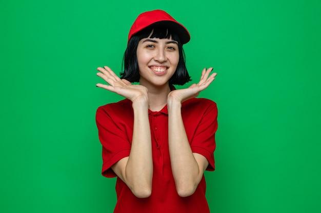 Souriante jeune femme de livraison caucasienne gardant les mains près de son visage et regardant