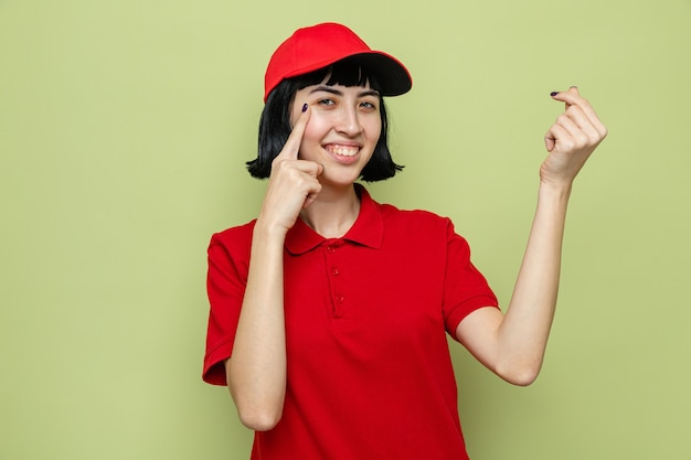 Souriante jeune femme de livraison caucasienne gesticulant de l'argent