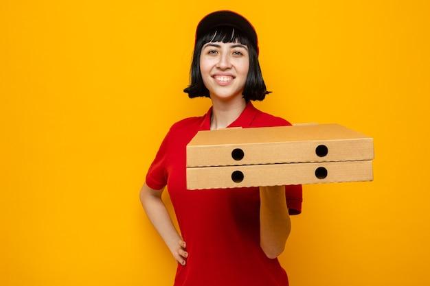 Souriante jeune femme de livraison caucasienne tenant des boîtes à pizza sur sa main