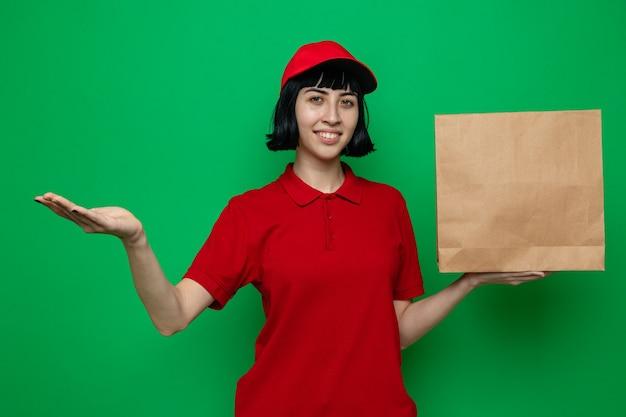 Souriante jeune femme de livraison caucasienne tenant un sac de nourriture en papier et gardant sa main ouverte
