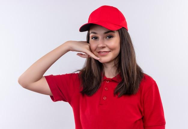 Souriante jeune femme de livraison portant un t-shirt rouge en bonnet rouge fait appel avec ses mains sur un mur blanc isolé