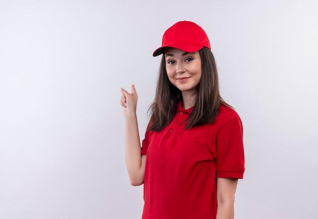 Souriante jeune femme de livraison portant un t-shirt rouge en bonnet rouge pointe vers l'arrière sur un mur blanc isolé