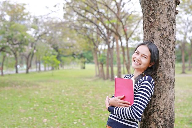 Souriante jeune femme avec un livre debout s'appuyer contre l'arbre du tronc dans le parc de l'été en plein air.