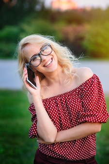 Souriante jeune femme à lunettes avec le téléphone à l'extérieur