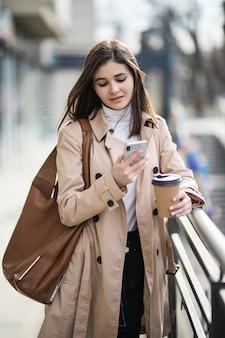 Souriante jeune femme en manteau marron clair dans la ville