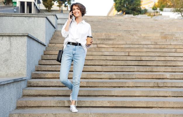Souriante jeune femme marchant en bas dans la rue