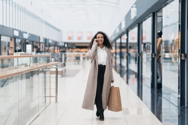 Souriante jeune femme marchant dans le hall du centre commercial