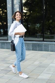 Souriante jeune femme marchant à l'extérieur dans la rue