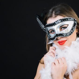 Souriante jeune femme en masque de carnaval tenant plume de boa sur fond noir