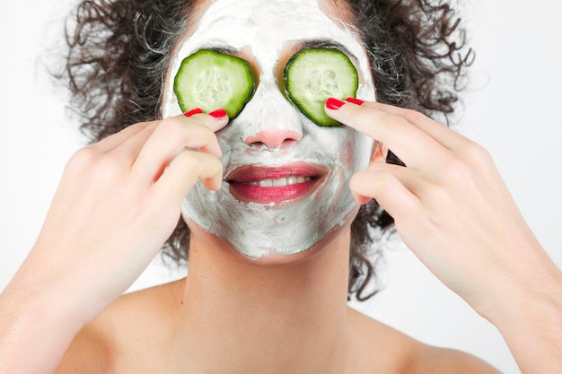 Souriante jeune femme avec masque facial mettant des tranches de concombre sur ses yeux