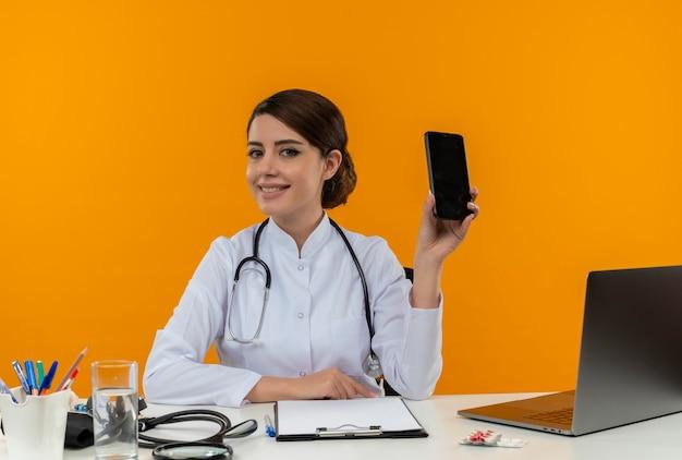 Souriante jeune femme médecin portant une robe médicale et un stéthoscope assis au bureau avec des outils médicaux et un ordinateur portable montrant un téléphone mobile isolé sur un mur jaune