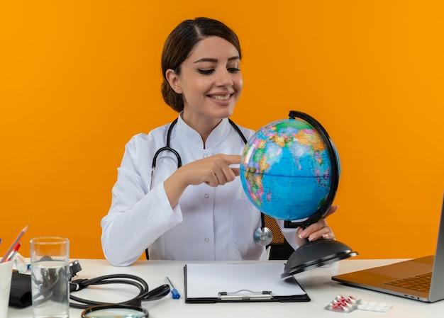 Souriante jeune femme médecin portant une robe médicale avec stéthoscope assis au bureau de travail sur ordinateur avec des outils médicaux tenant et mettant le doigt sur le globe sur fond jaune d'isolement