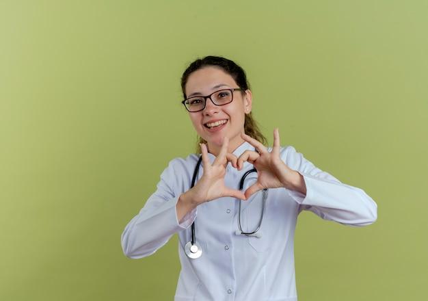 Souriante jeune femme médecin portant une robe médicale et un stéthoscope avec des lunettes montrant le geste du cœur isolé sur un mur vert olive