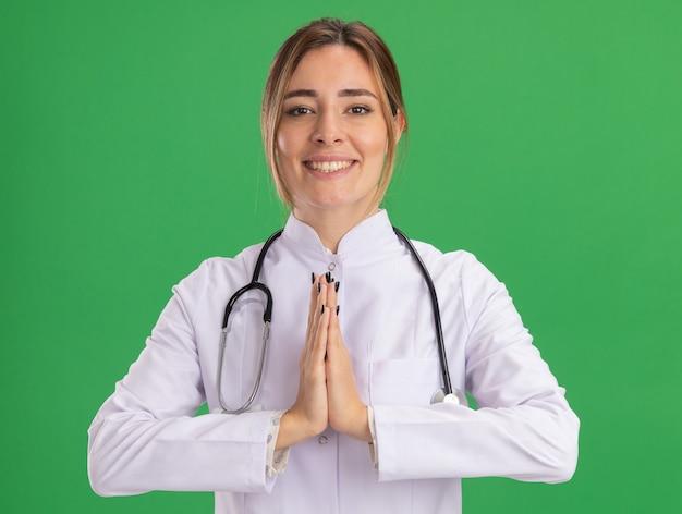 Souriante jeune femme médecin portant une robe médicale avec stéthoscope montrant le geste de prier isolé sur le mur vert