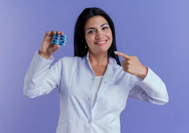 Souriante jeune femme médecin portant une robe médicale tenant et pointant sur pack de capsules médicales à la recherche