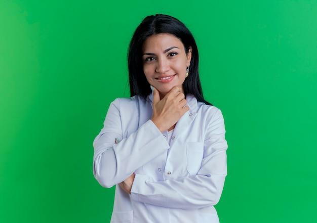 Souriante jeune femme médecin portant une robe médicale touchant le menton isolé sur un mur vert avec espace copie