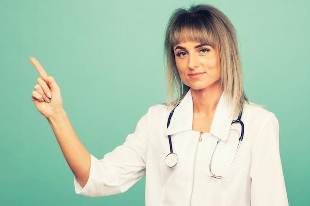 Souriante jeune femme médecin avec un stéthoscope pointe ses doigts sur un espace bleu